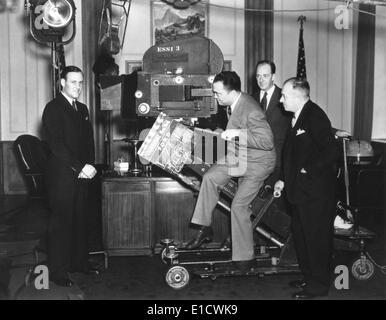 El Director del FBI, J. Edgar Hoover con un noticiario cámara en Universal Studios. Clyde Tolson, Hoover's FBI colega Foto de stock