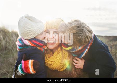 Mitad mujer adulta con hijo e hija besar su mejilla en la costa Foto de stock