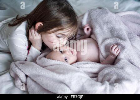 Niña besar la mejilla del hermano bebé en la cama Foto de stock