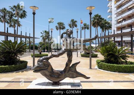 Hombre encima Dolphin estatua de Salvador Dalí en Marbella Foto de stock