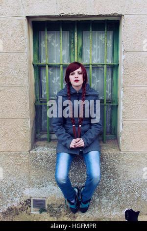Joven pelirroja mujer, con dos largas trenzas, sentarse cerca de una ventana vieja Foto de stock