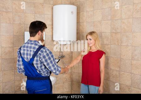 Manos plomero a trabajar en un cuarto de baño, servicio de ...