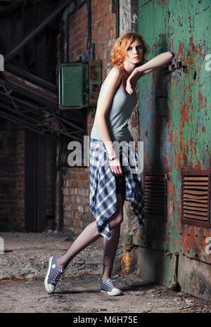 Retrato de una joven y bella grunge (rock) chica en camisa a cuadros y desgarrada pantyhose Foto de stock