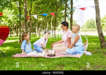 Tres jóvenes y una mujer con un picnic en el césped en el parque público no lejos de playground Foto de stock