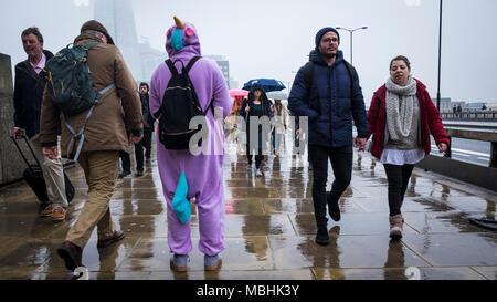 Londres, Reino Unido. 11 de abril de 2018. El clima del REINO UNIDO: Un recaudador de fondos para la Meningitis Research Foundation está sobre el puente de Londres, ya que pasar los viajeros hacen su camino al trabajo en un día en la capital drizzly (c) Pablo Swinney/Alamy Live News Foto de stock