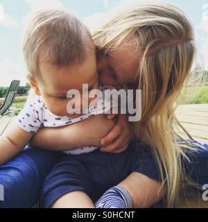 Niña besando y abrazando a su hermano bebé Foto de stock