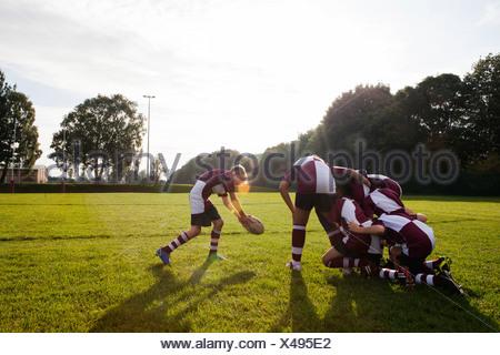 Equipo de rugby colegial adolescente tomando la bola de grupito Foto de stock