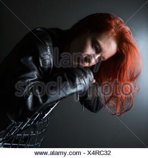 Hermosa joven pelirroja mujer vistiendo chaqueta de cuero colgando en la parte posterior de la silla Foto de stock