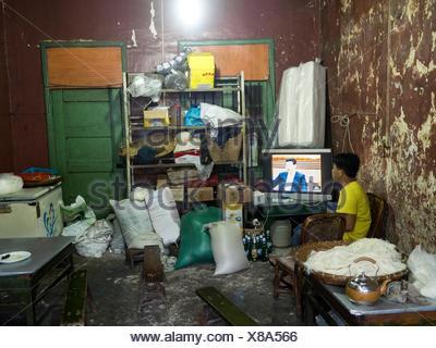 Un hombre ve la televisión en una cocina sucia en Sudian Foto ...