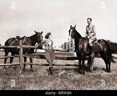 Années 1930 Années 1940 Équipement d'ÉQUITATION EN COUPLE MAN RIDING HORSE WOMAN STANDING BY CLÔTURE EN BOIS Banque D'Images