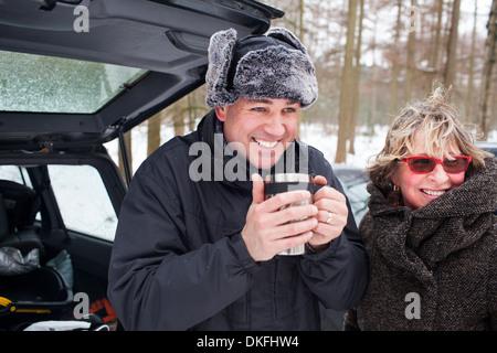 La mère et le fils d'avoir une boisson chaude à l'extérieur en hiver Banque D'Images