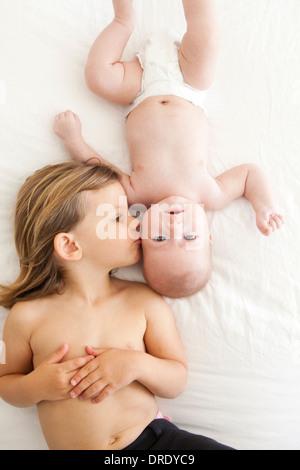 Soeur de l'embrasser plus jeune enfant Banque D'Images