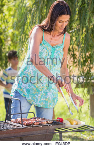 Woman Cooking Barbeque In Countryside Banque D'Images