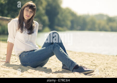 Jolie jeune fille hipster reposant à la plage. Portrait femme assise sur le sable près de l'eau. Banque D'Images