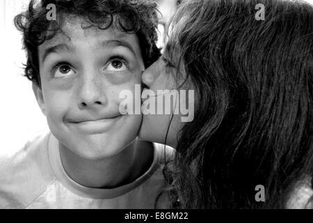 Girl kissing boy sur la joue Banque D'Images