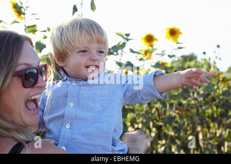 Mid adult woman and toddler fils pointant dans champ de tournesol Banque D'Images