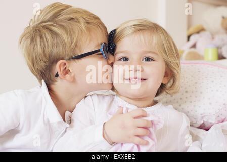 Boy kissing sister's cheek Banque D'Images