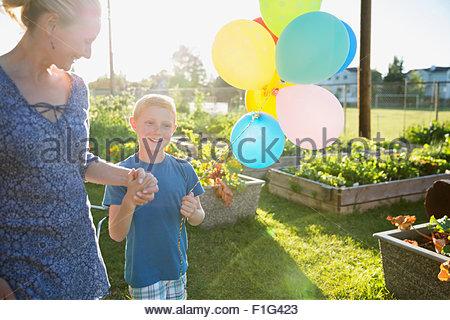 Mère et fils avec des ballons dans le jardin ensoleillé Banque D'Images
