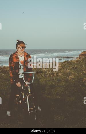 Teenage girl sitting sur un vélo par la côte Banque D'Images