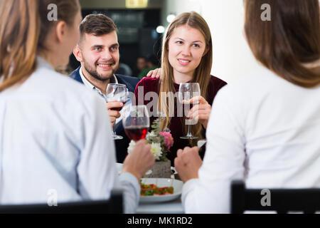Les amis sont en train de dîner dans le restaurant à l'intérieur. Banque D'Images
