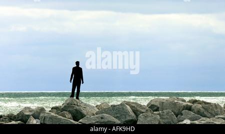 Silhouette di un giovane uomo in piedi sulle rocce sul lungolago del Lago Michigan Foto Stock