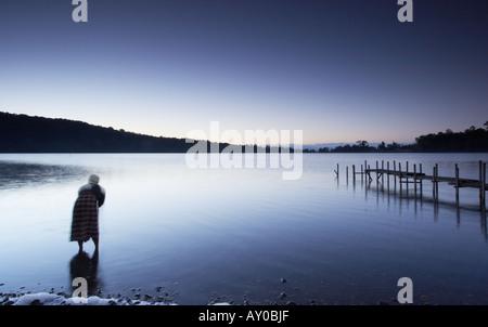 Lavaggio uomo nel lago all'alba, Bali Foto Stock
