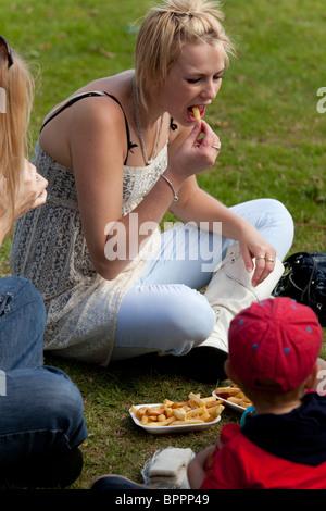 Ragazza sedeva su erba mangiare patatine a una fiera di paese Foto Stock