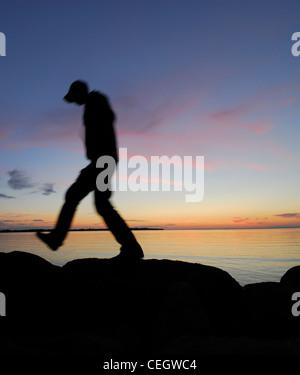 Silhouette di uomo a camminare da un lago di notte Foto Stock