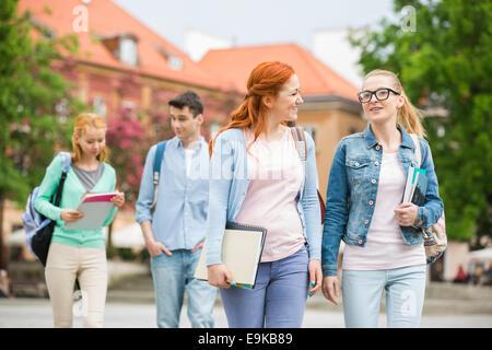 Giovani amici universitari camminando sulla strada Foto Stock