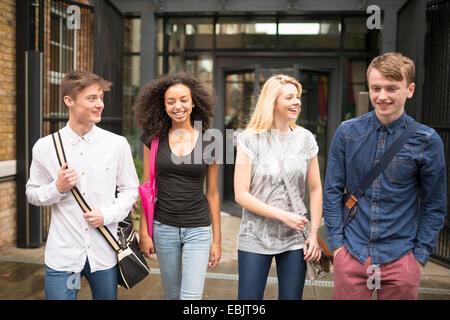 Quattro amici a piedi e sorridente Foto Stock