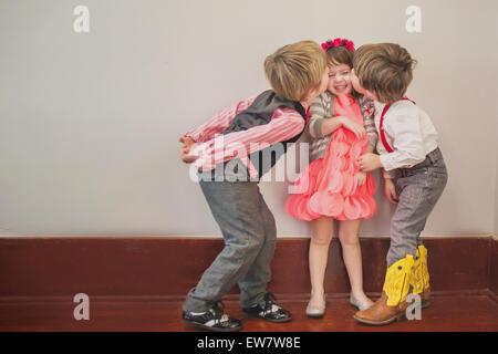 Due ragazzi baciare una ragazza sulla guancia Foto Stock