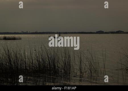 Silhouette uomo sulla barca al lago Foto Stock