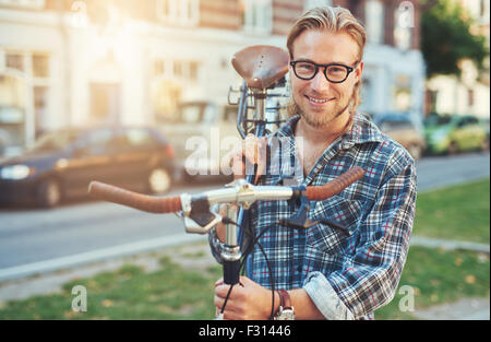 Giovane uomo lo stile di vita della città. trasporto bici sulla sua spalla. ritratto sorridente Foto Stock