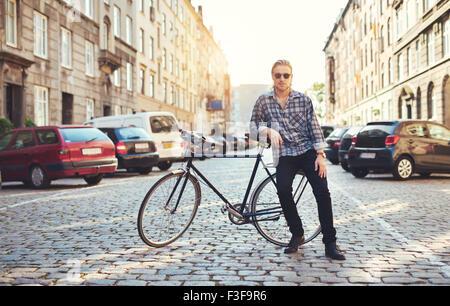 Vivere in città, Ritratto di giovane uomo seduto sulla sua moto Foto Stock