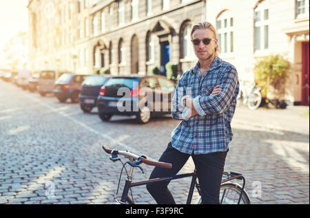 Ritratto di uomo sulla sua bicicletta con le braccia incrociate cercando elegante stile di vita della città Foto Stock