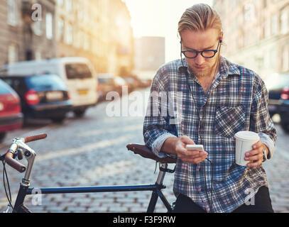Outdoor ritratto della moderna giovane con telefono cellulare in strada, seduto sulla bici Foto Stock