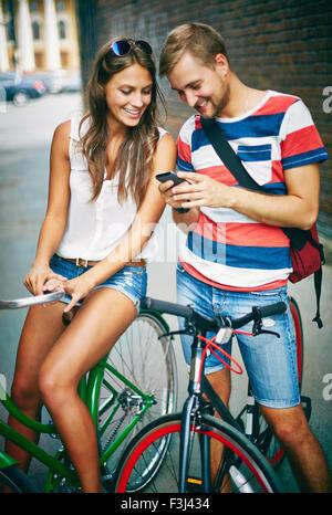 Coppia giovane sulle biciclette tramite cellulare all'aperto Foto Stock
