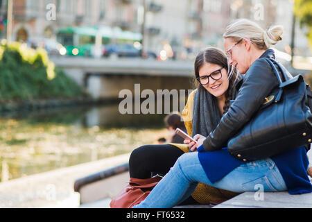 Donna matura che mostra smart phone su amico seduti sui gradini Foto Stock