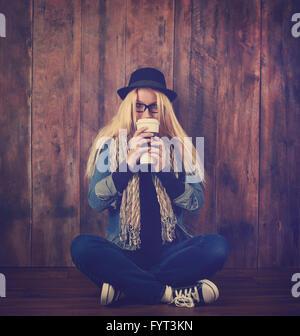 Una giovane donna tanga è bere una bevanda di caffè contro uno sfondo di legno. Ella ha occhiali e un cappello a. Foto Stock