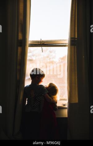 Bambini abbracciando accanto alla finestra dim spazio Foto Stock