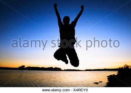 Willmar, Minnesota, Stati Uniti d'America; silhouette di una persona di saltare in aria dall'acqua al tramonto Foto Stock