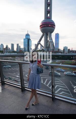 Jovem mulher tendo selfie perto do rádio e tv ORIENTAL PEARL TOWER, famosa atracção turística localizada no novo Foto de Stock
